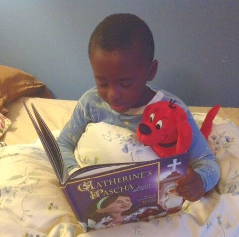 "A child sitting in bed and reading Catherine's Pascha, with a plush red dog under his arm ""reading"" with him."