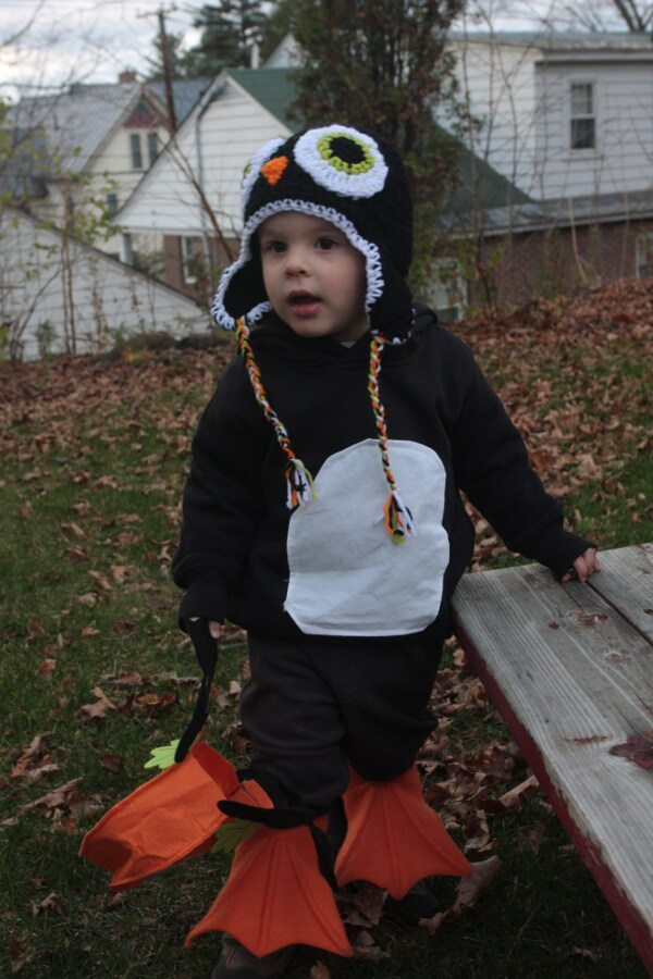 A small cild in a Halloween costume standing in his back yard. The costume is a penguin, made from a black sweatsuit and swimming flippers.